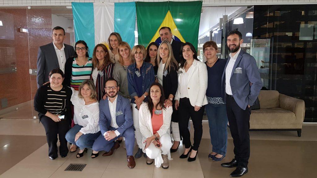 grupo de profissionais da odontologia reunidos  para a foto. Ao fundo estendida a bandeira da Argentina e do Brasil
